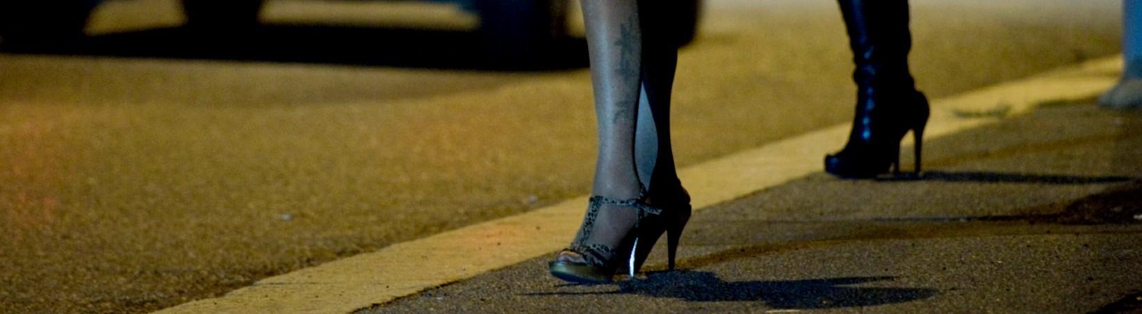 Beine von zwei sich prostituierenden Frauen an einer Straße.
