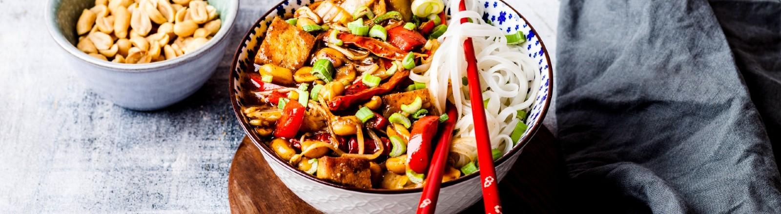 Eine Schale mit Gemüse, Reisnudeln, Tofu und Erdnüssen.