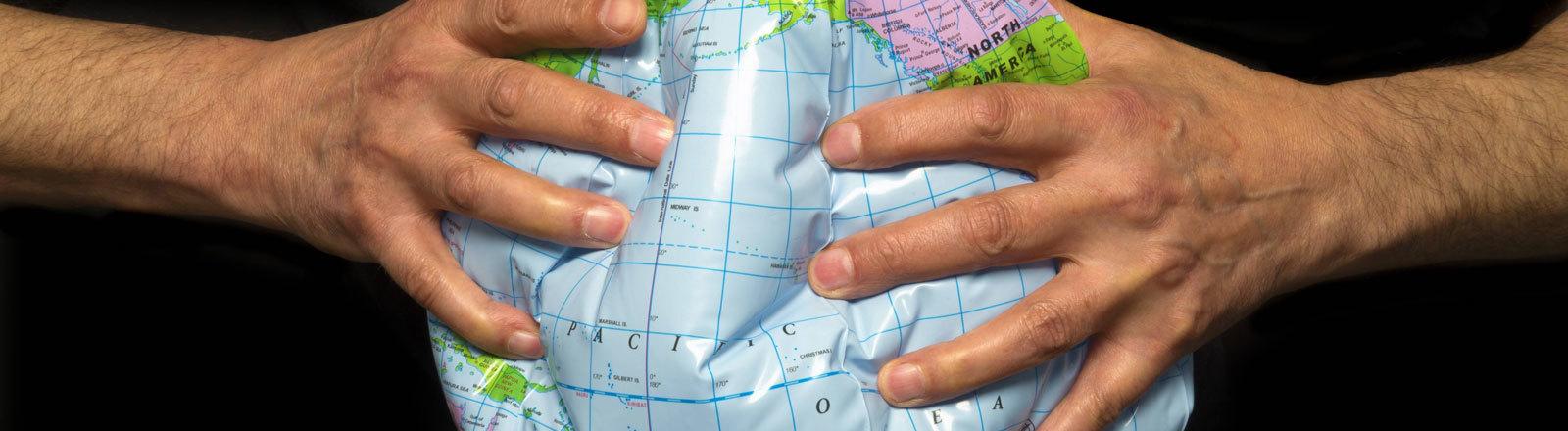 Ein Mann presst mit seinen Händen einen aufblasbaren Globus zusammen.
