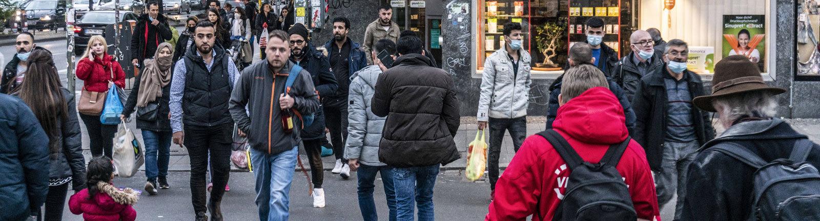 Menschen überqueren eine Straße am Hermannplatz im Stadtteil Neukölln in Berlin.