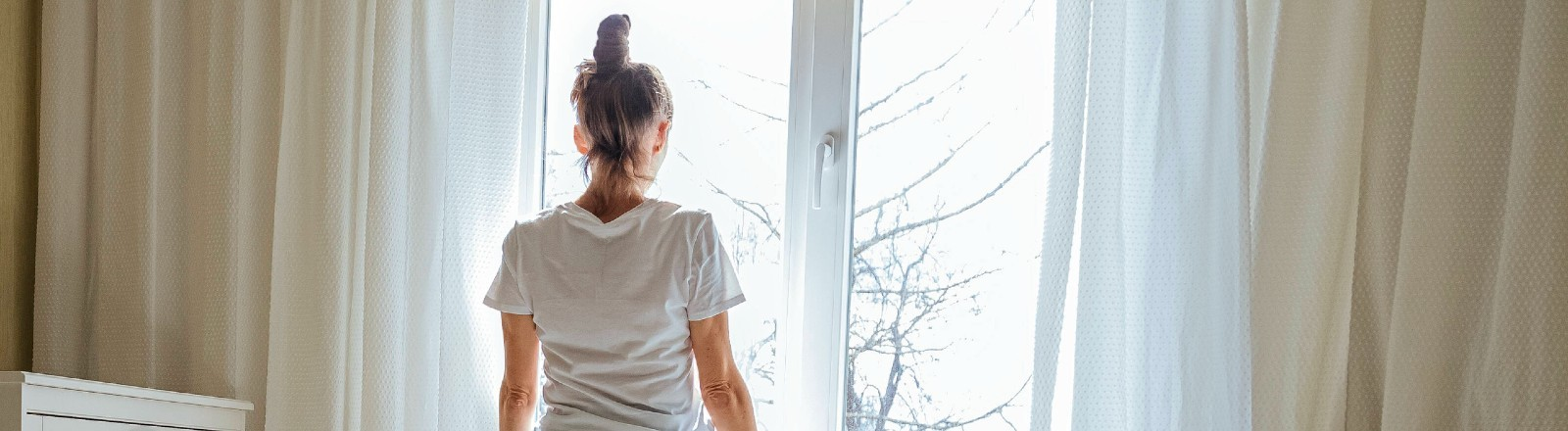 Eine Frau schaut aus dem Fenster.