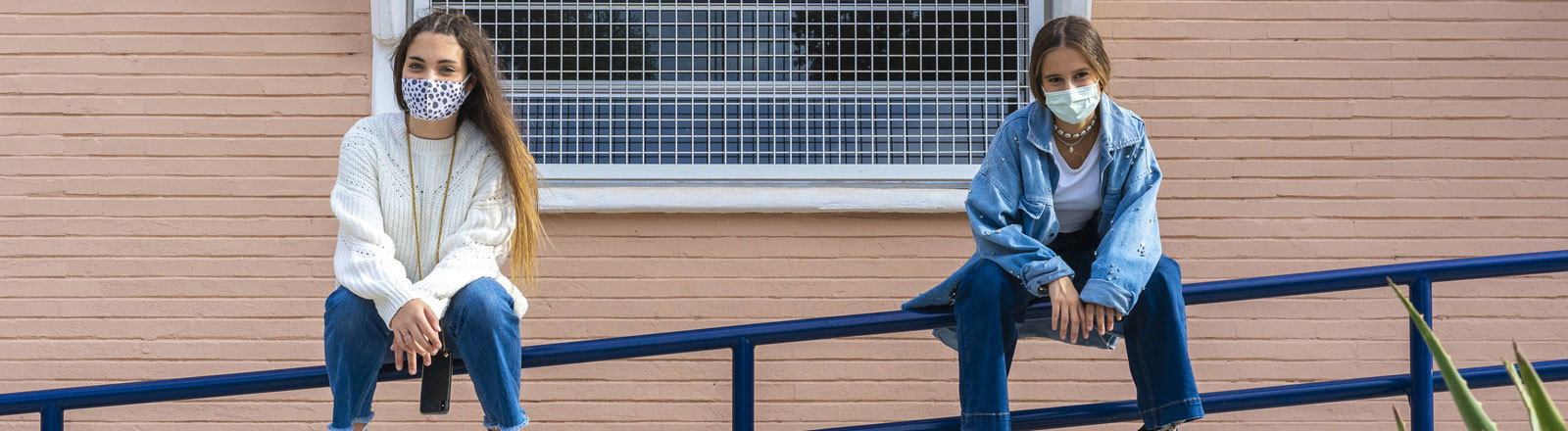 Zwei jugendliche Frauen sitzen mit Abstand zueinander auf einem Treppengeländer.