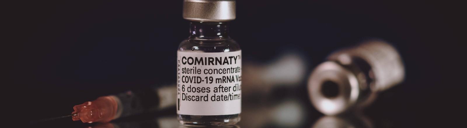 Fläschchen mit Impfstoff von Biontech/Pfizer, daneben liegt eine Spritze.