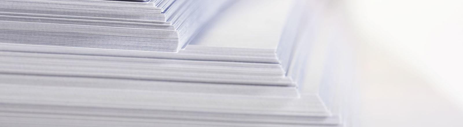 Ein Stapel mit Papier, der wissenschaftliche Publikationen symbolisieren soll.