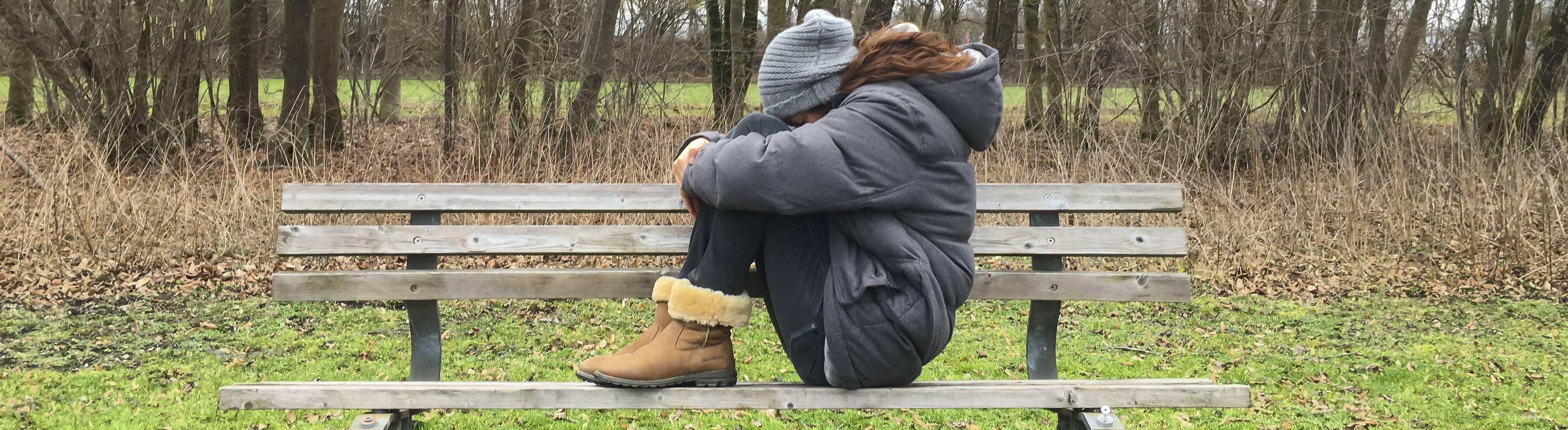 Frau sitzt auf einer Bank, die Hände um die Knie geschlungen. Im Hintergrund kahle Bäume