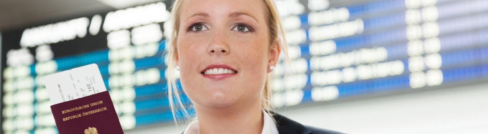 Frau mit Reisepass in der Hand am Flughafen