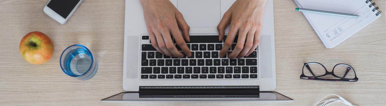 Hände tippen auf einem Laptop.