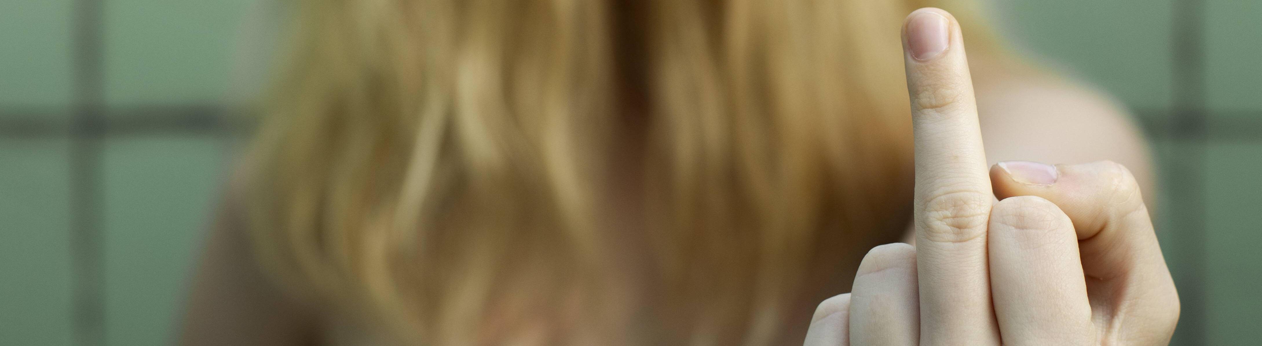 Nackte Frau mit Haaren vorm Gesicht, die den Mittelfinger in die Kamera streckt.