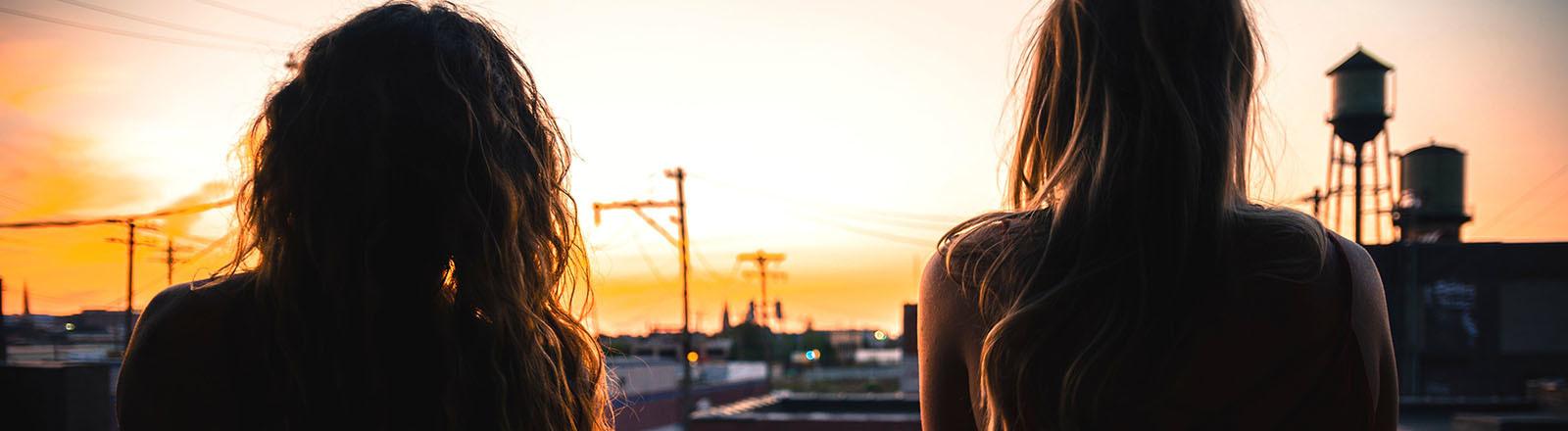 Zwei Frauen schauen in den Sonnenuntergang.