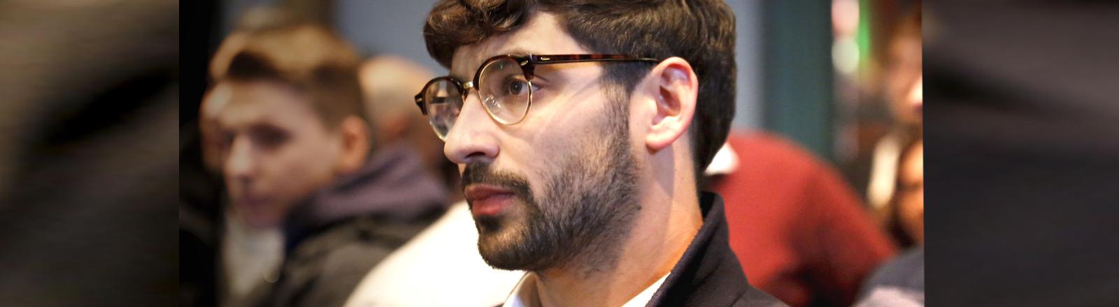 Ein junger Mann mit Bart und Brille