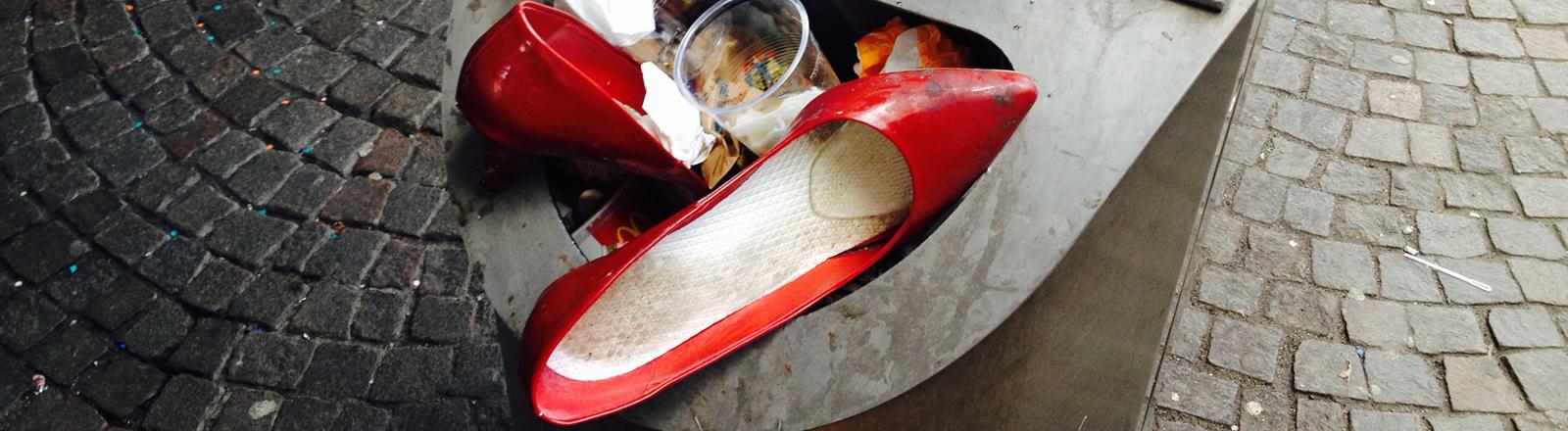 Reste vom Karneval oder einfach nur beim Stadtbummel durchgelaufene Damen-Schuhe stecken in einem Abfallkorb in Köln.