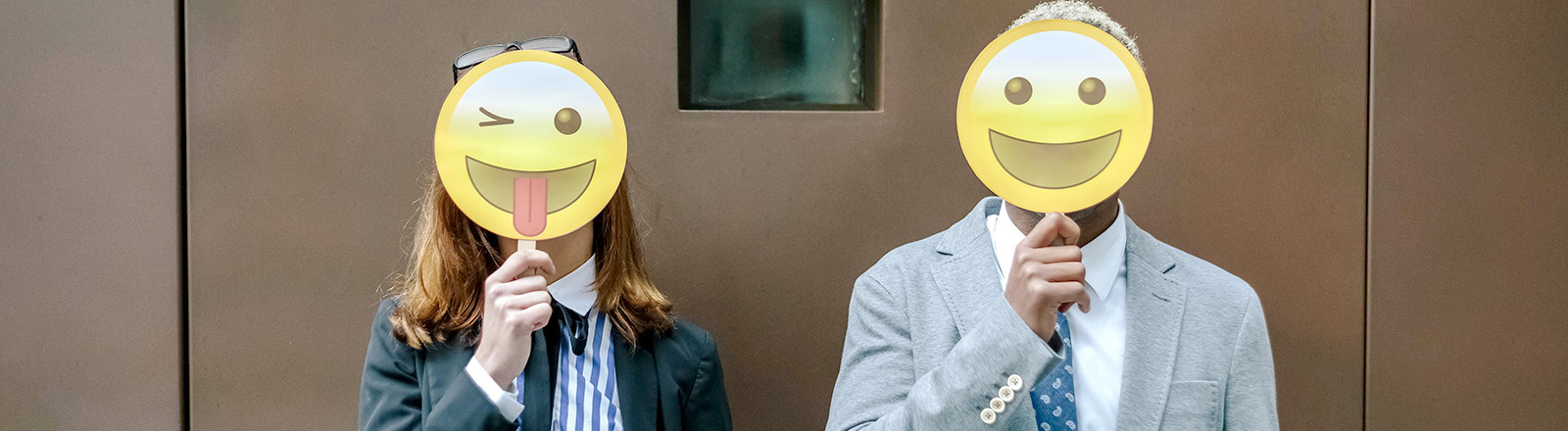 Mann und Frau halten sich lachende Masken vors Gesicht