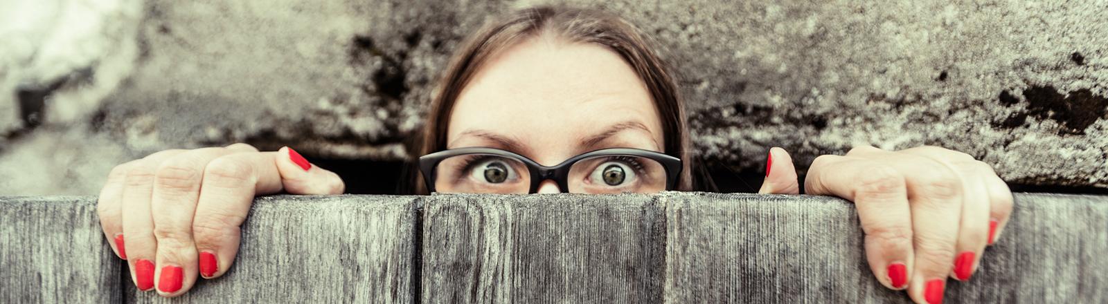 Frau guckt über eine Mauer.