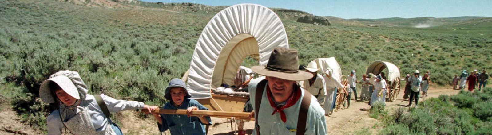 Eine Gruppe von in historischen Kostümen gekleideten Mormonen zieht am 14.07.1997 nahe der Ortschaft The Needles (US-Bundesstaat Wyoming) Handkarren durch die Steppe.
