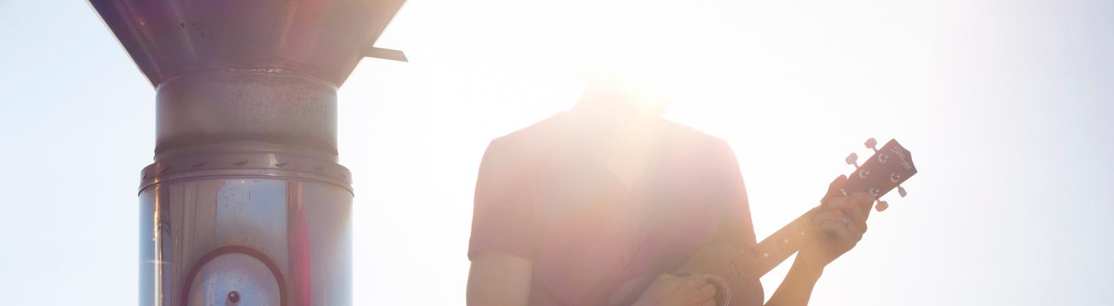 Ein Mann mit Ukulele im Gegenlicht