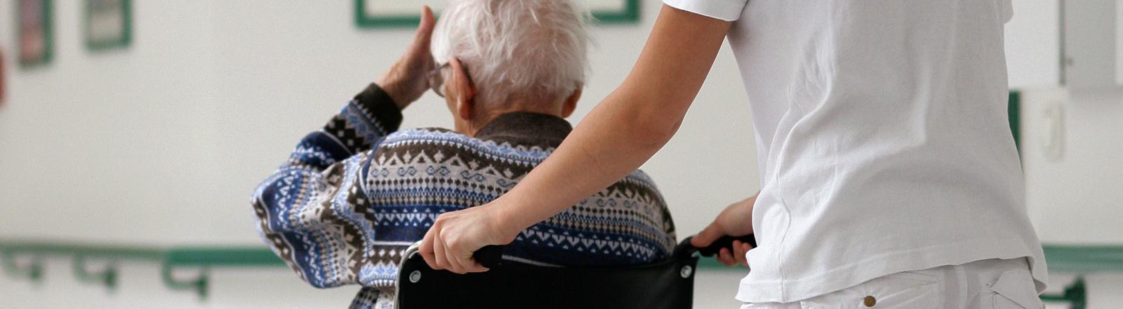 Pflegerin schiebt einen alten Mann im Rollstuhl vor sich her.