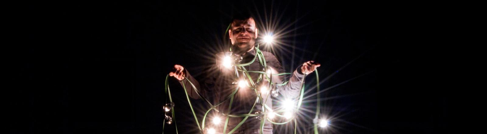 Mensch in eine Lichterkette gewickelt