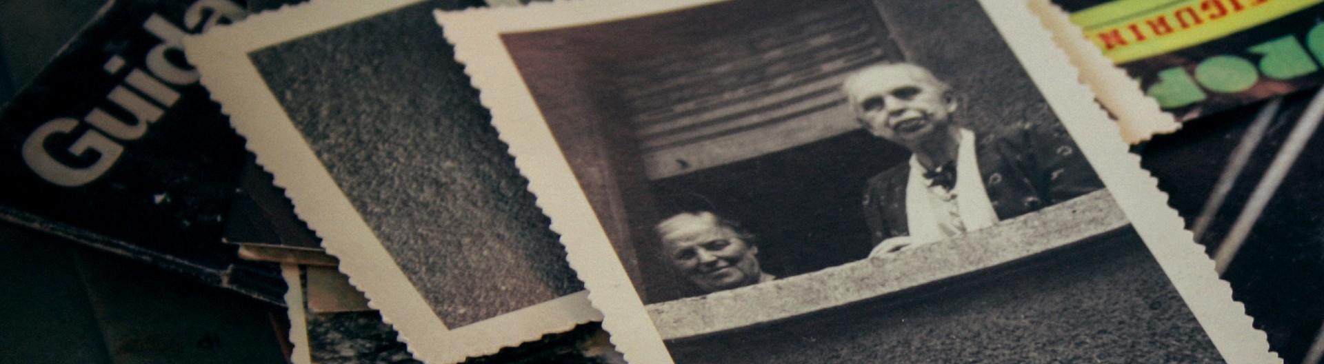Ein Stapel alte Fotos, einige in schwarz-weiß mit einem gezackten Rand