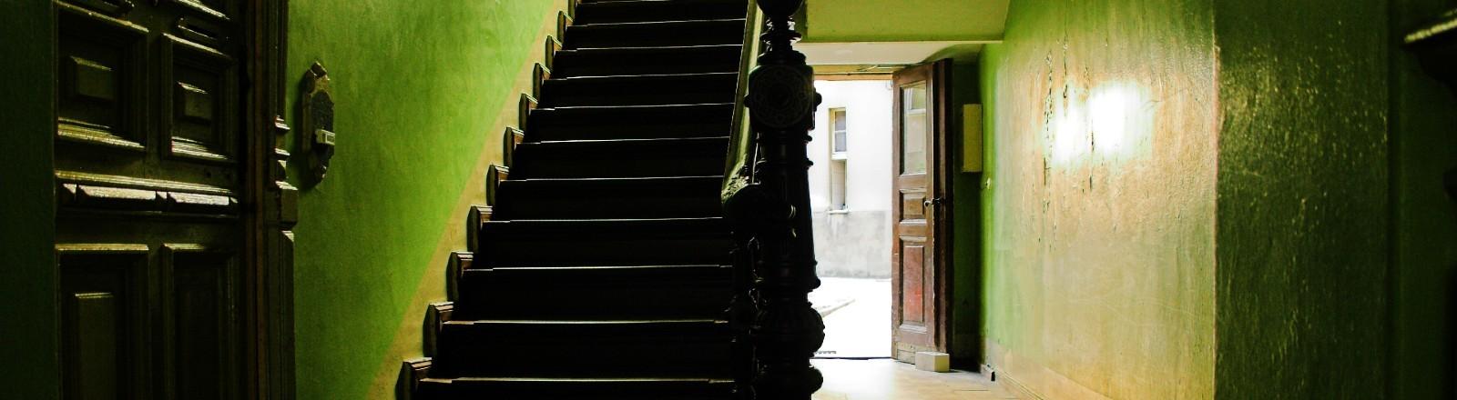 Treppenhaus mit alter Holztreppe, schummeriges Licht, eine Tür nach draußen ist geöffnet