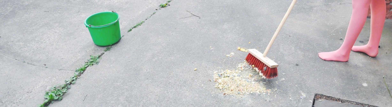 Frau in Strumpfhosen fegt Späne auf einem Betonboden