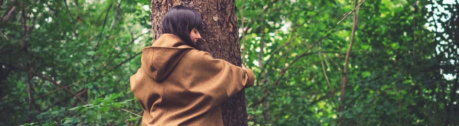 Frau im Wald, die einen Baum umarmt.