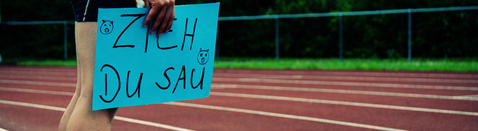 """Sportler am Rand einer Laufbahn mit einem Schild auf dem """"Zieh Du Sau"""" steht"""