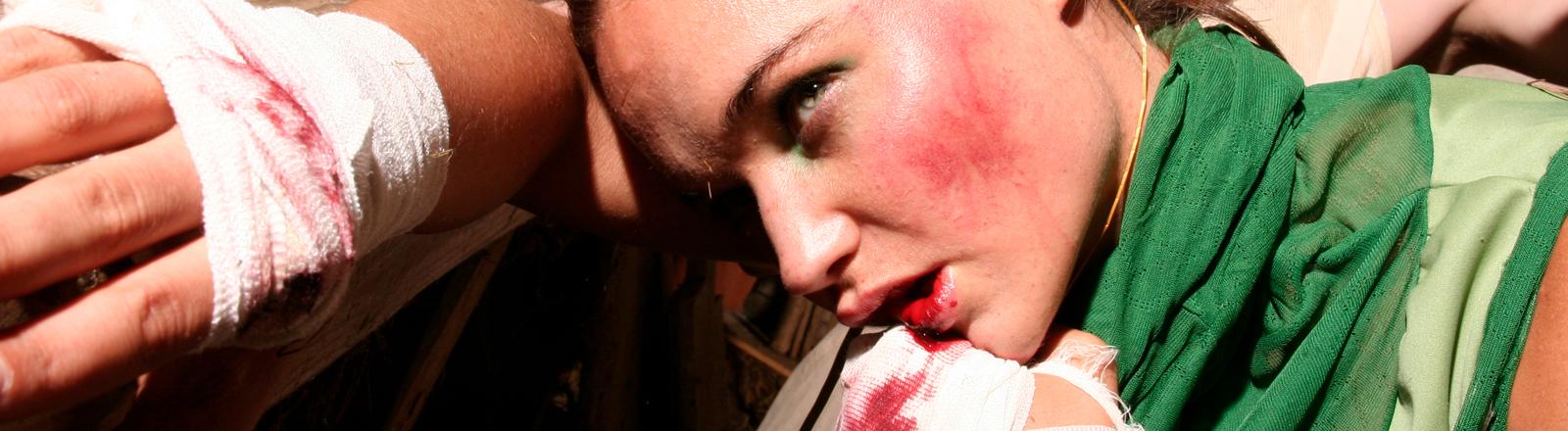 Ein Frau mit Kampfspuren im Gesicht
