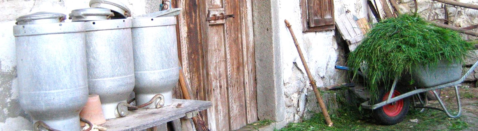 Schubkarre auf Bauernhof vor einem Schuppen.