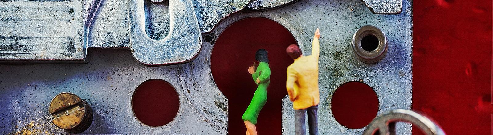 Eine männliche Figur weist einer weiblichen Figur den Weg in einem Schlosskasten
