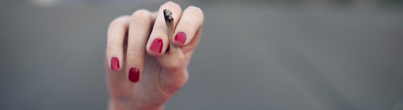 Hand mit lackierten Nägeln, die einen Joint hält