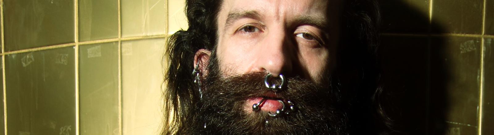 Mann mit Bart und Piercings lehnt an einer Wand
