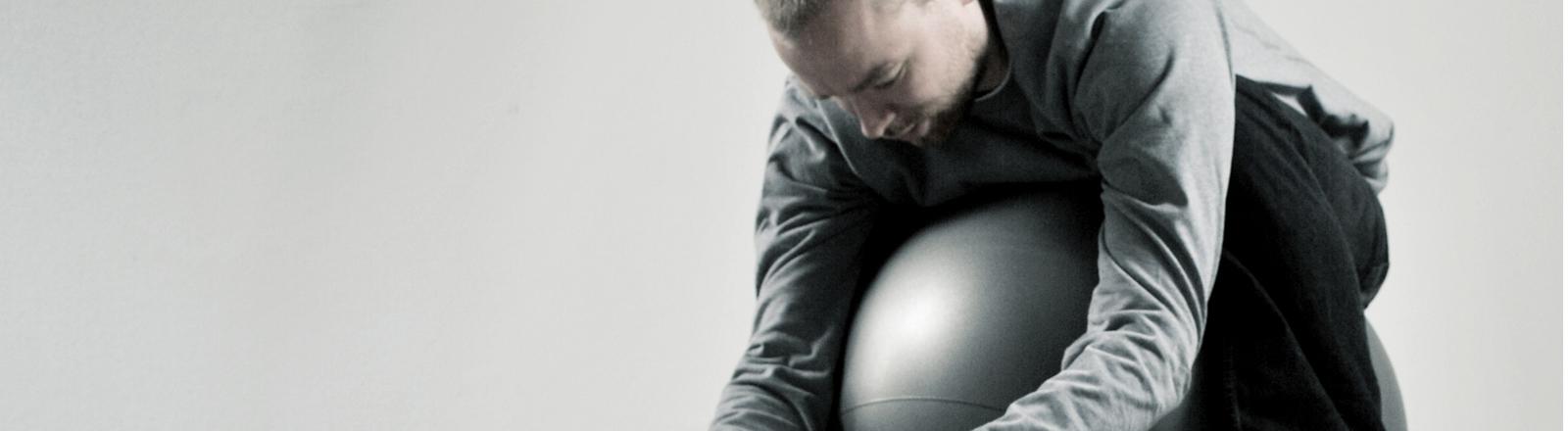 Ein Mann liegt auf einem Gymnastikball