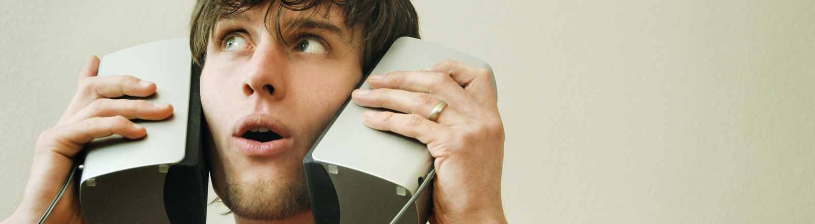 Ein junger Mann hält sich zwei Computerboxen an die Ohren.