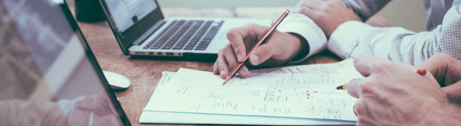 Zwei Männer sitzen an ihren Computern und schreiben Notizen auf ein Blatt Papier.
