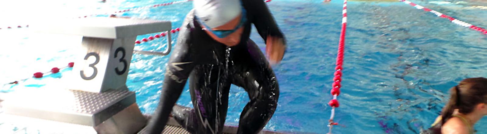 Frau im Neo steig aus dem Wasser