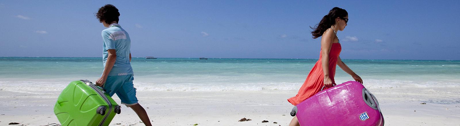 Zwei Menschen am Strand gehen in verschiedene Richtungen.