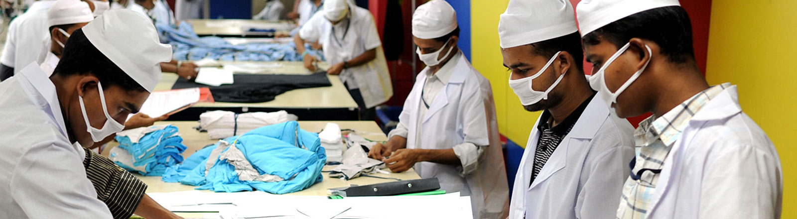 Arbeiter mit Mundschutz bei der Textilbearbeitung in Bangladesh
