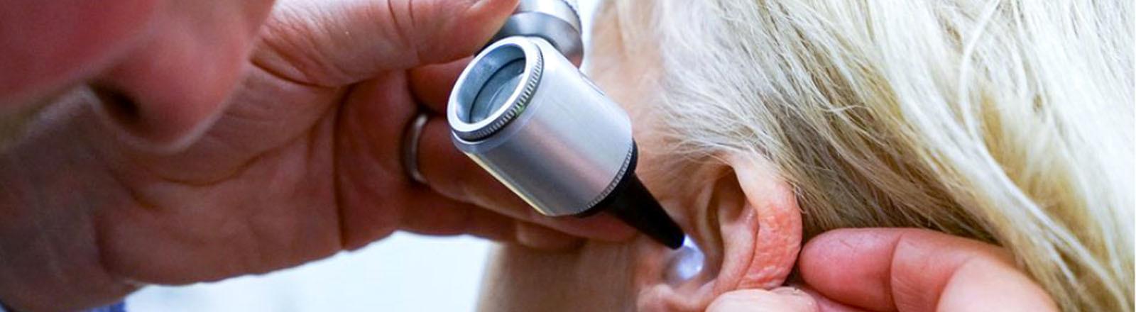 Ohrenartz schaut in das Ohr einer Patientin.