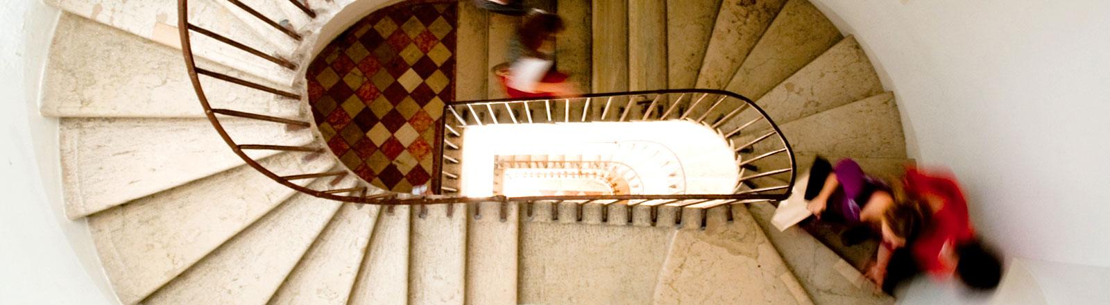 Altes Treppenhaus, zwei Menschen huschen durchs Bild