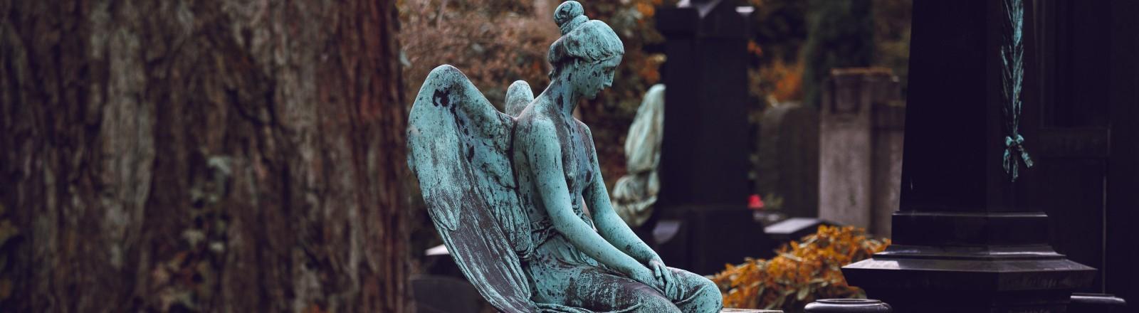 Die Statue eines Engels aufs einem Grabstein.