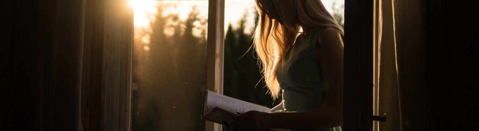 Eine Frau sitzt an einem geöffneten Fenster und liest ein Buch.