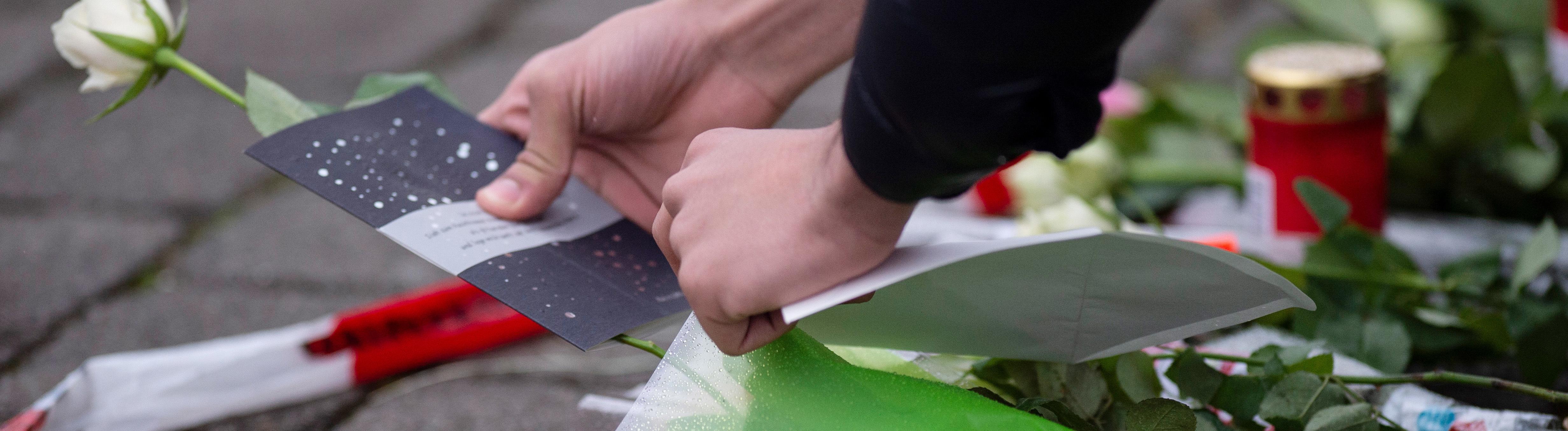 20.02.2020, Hessen, Hanau: Eine Frau legt als Zeichen der Trauer eine Karte und Blumen an einem Tatort in Kesselstadt nieder.
