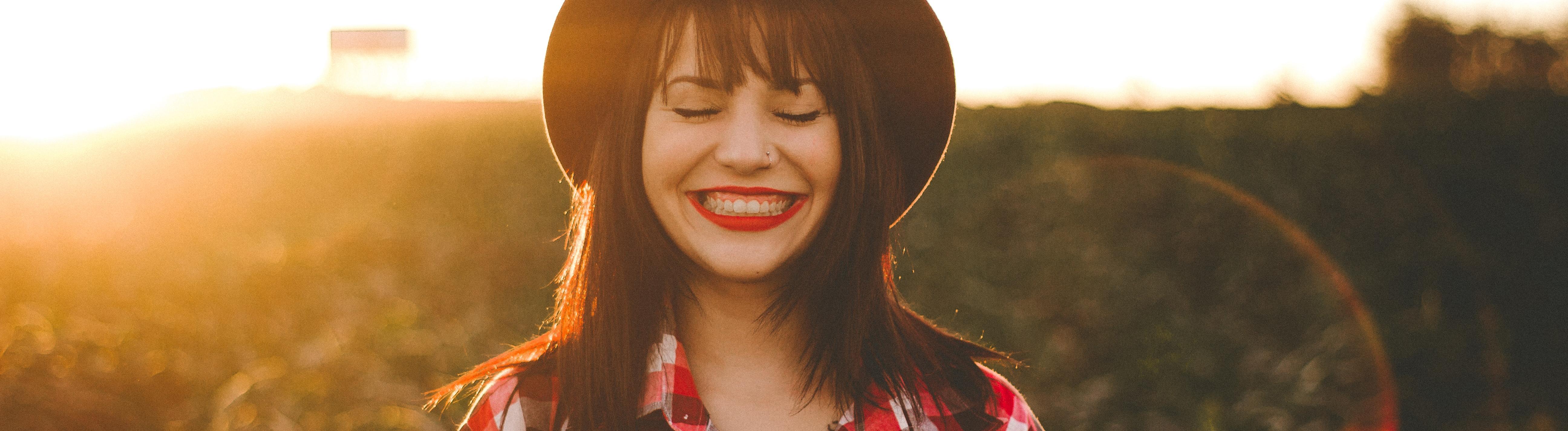 Eine Frau mit Hut lächelt