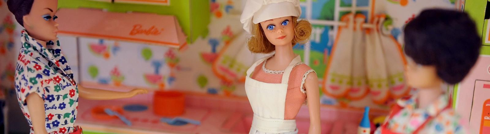 Drei Barbiepuppen in einer Küche. Symbolbild für Hausfrauen.