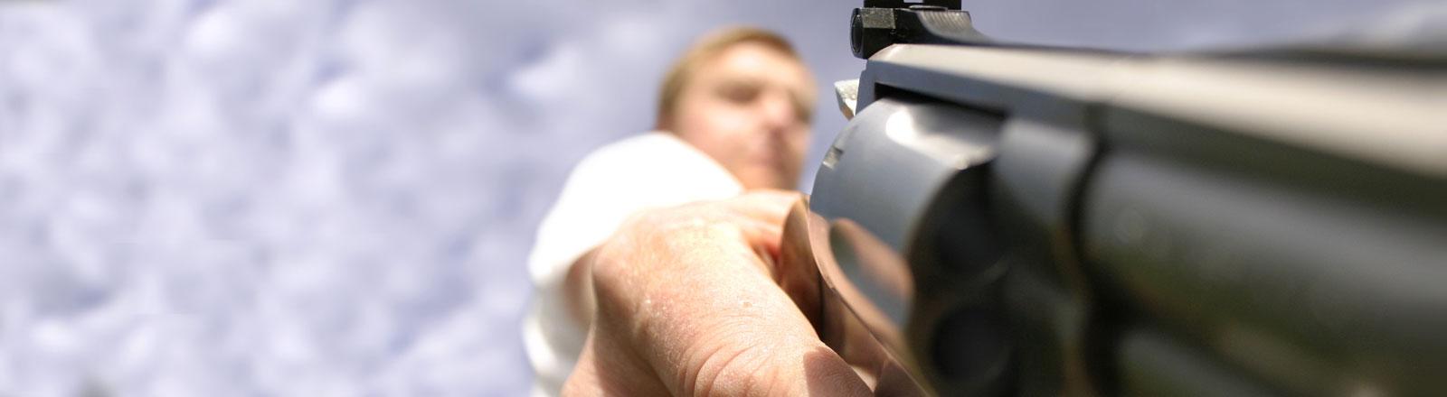Ein Mann hält eine Waffe in der Hand, die auf den Boden gerichtet ist.