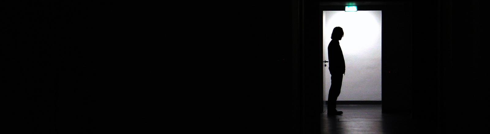 Person steht in der Tür eines dunklen Raums