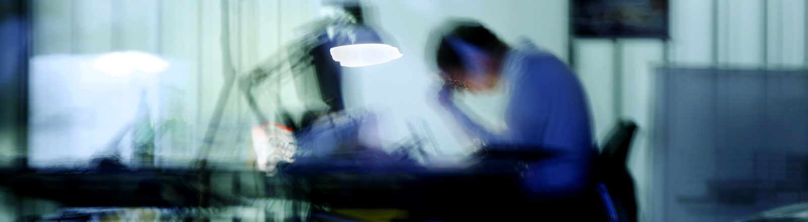Ein Mann sitzt abends an einem Schreibtisch, die Schreibtischlampe ist angeschaltet.