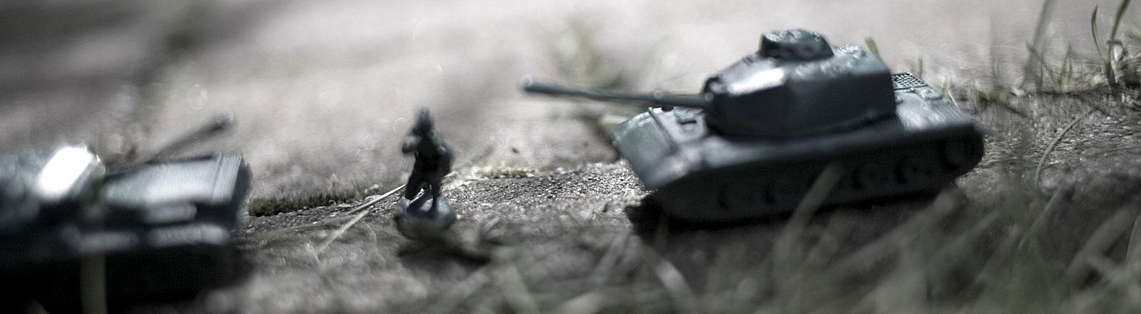 Zwei Spielzeugpanzer bedrohen einen Spielzeugsoldaten