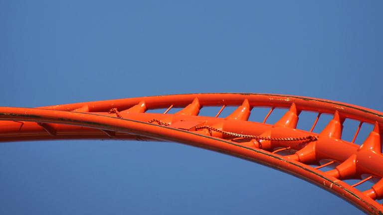 Teil der Bahn einer Achterbahn in orange vor blauem Himmel.