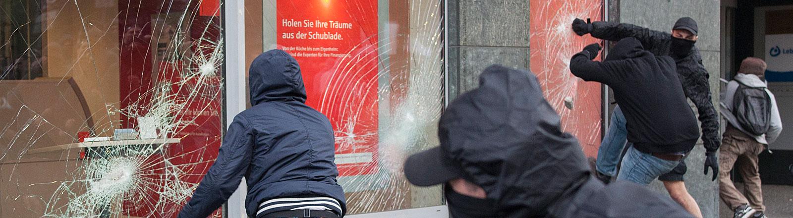 """Teilnehmer der """"Revolutionären 1. Mai-Demonstration"""" treten am 01.05.2013 in Berlin das Schaufenster einer Sparkassenfiliale ein."""